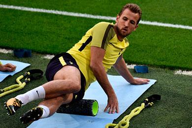 Futbolista haciendo estiramientos con el rodillo de espuma