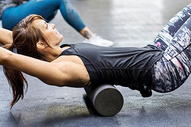 Mujer haciendo ejercicio con un Foam Roller